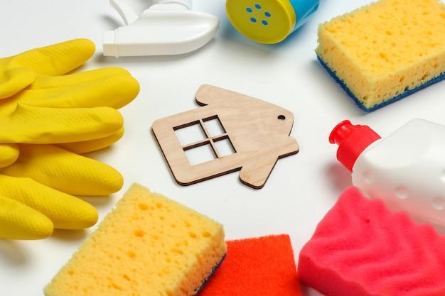 Concetto di pulizie. set di prodotti per la pulizia e la figura della casa su sfondo bianco.