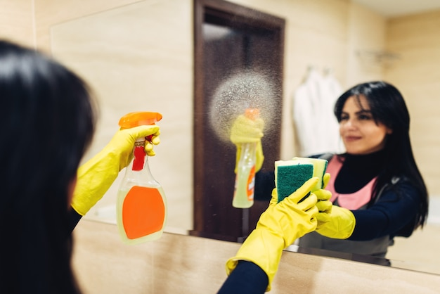Le mani della cameriera in guanti di gomma puliscono lo specchio con uno spray detergente, l'interno del bagno dell'hotel. servizio di pulizia professionale, donna di servizio, lavorazioni sanitarie