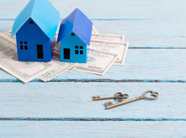 Case fatte di carta, chiavi e denaro su uno spazio di legno