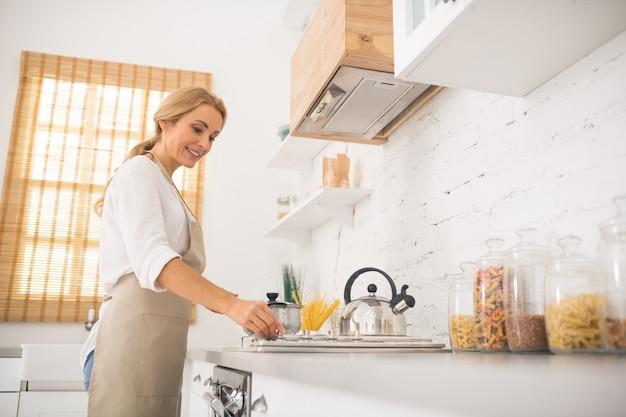 Casalinga in grembiule che cucina in cucina