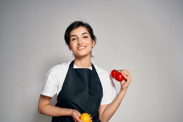 Casalinga in un grembiule nero in cucina che taglia le verdure mangiando sano