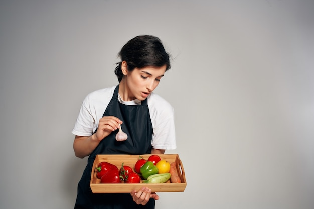 Casalinga in grembiule nero verdure cibo fresco sfondo chiaro