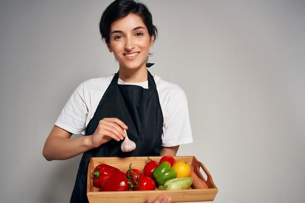 Casalinga in un grembiule nero con verdure cucina sana