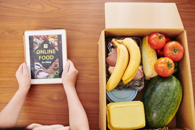 Casalinga che controlla l'applicazione di consegna di cibo in linea sul computer tablet e disimballaggio grande scatola di generi alimentari