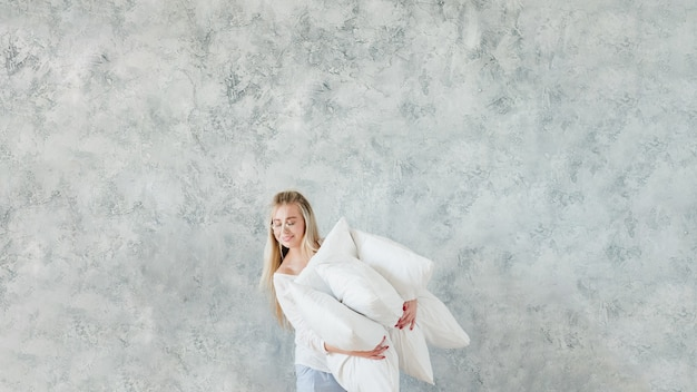 Scelta casalinga. signora felice che tiene il mucchio del cuscino della piuma.