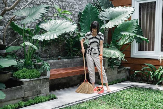Casalinga che pulisce un cortile con spazzare le foglie sul marciapiede del cortile