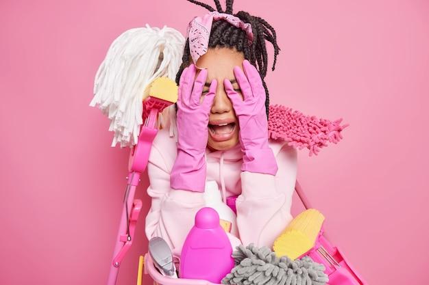 Casalinga contro faccia con le mani piange dalla disperazione indossa guanti di gomma protettivi ha molto lavoro sulla casa che è stanca di pulire usa mop diversi detergenti isolati su rosa