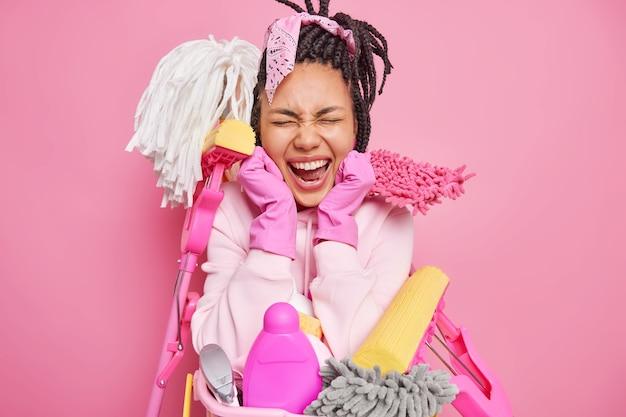 La casalinga esprime emozioni positive circondata da strumenti di pulizia riordina gli strumenti indossa guanti di gomma isolati su rosa