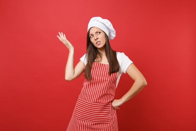 Cuoco o fornaio femminile della casalinga in grembiule a strisce, t-shirt bianca, cappello da cuoco unico del toque isolato sul fondo rosso della parete. la donna sconvolta triste attraente della governante ha sollevato la mano su. deridere il concetto dello spazio della copia.