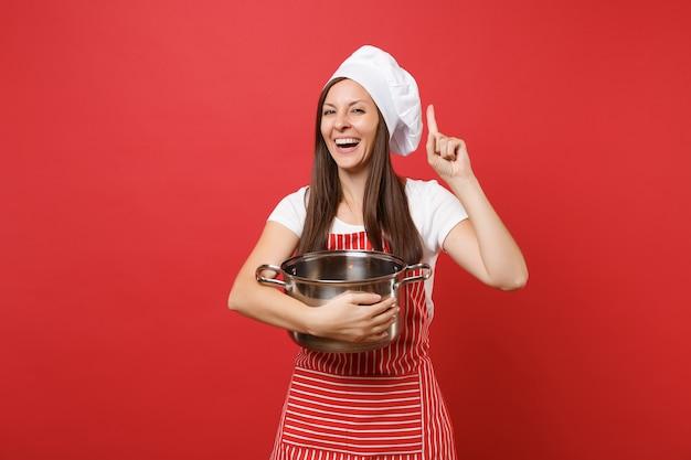 Cuoco o fornaio femminile della casalinga in cappello da cuoco unico del toque della maglietta bianca del grembiule a strisce isolato sul fondo rosso della parete. bella donna della governante che tiene il vaso vuoto delle terrecotte. mock up copy space concept
