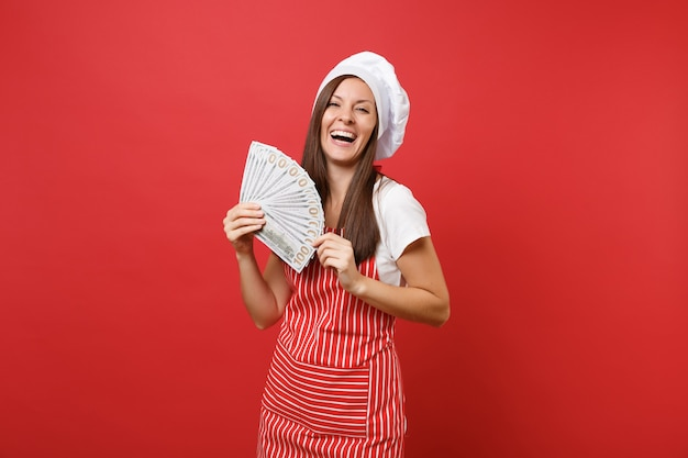 Donna casalinga chef cuoco panettiere in grembiule a righe bianco t-shirt toque cappello chef isolato su sfondo rosso parete. donna emozionante che tiene un sacco di banconote in dollari denaro contante. deridere il concetto dello spazio della copia.