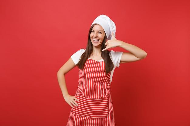 Cuoco o fornaio femminile della casalinga in grembiule a strisce, t-shirt bianca, cappello da cuoco unico del toque isolato sul fondo rosso della parete. donna divertente che fa il gesto del telefono come dice di richiamarmi. deridere il concetto dello spazio della copia.