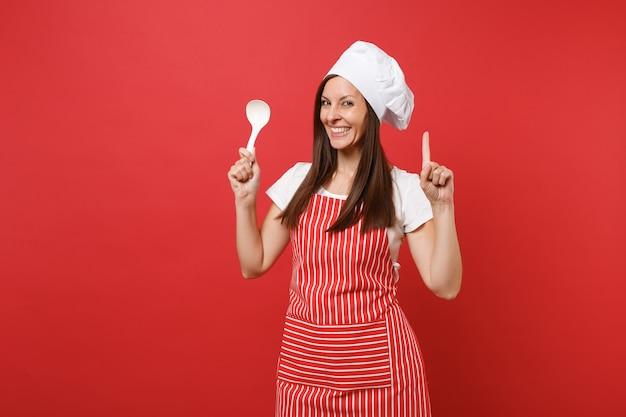 Cuoco o fornaio femminile della casalinga in grembiule a strisce, maglietta bianca, cappello del cuoco unico di toque isolato sul fondo rosso della parete. degustazione della stretta della donna della governante con il mestolo di minestra. deridere il concetto dello spazio della copia.