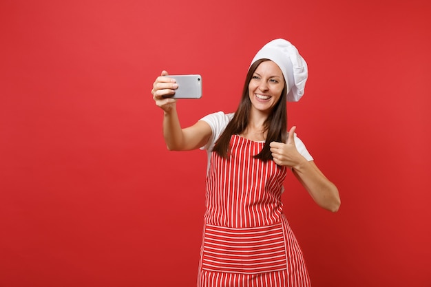 Cuoco o fornaio femminile della casalinga in grembiule a strisce, t-shirt bianca, cappello da cuoco unico del toque isolato sul fondo rosso della parete. sorridente donna divertente facendo selfie girato sul telefono cellulare. deridere il concetto dello spazio della copia.