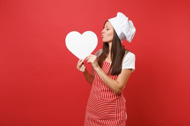 Cuoco o fornaio femminile della casalinga in grembiule a strisce, t-shirt bianca, cappello da cuoco unico del toque isolato sul fondo rosso della parete. la donna sorridente della governante tiene l'area di lavoro vuota del cuore. deridere il concetto dello spazio della copia.
