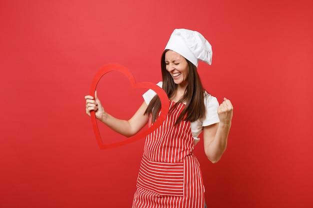 Cuoco o fornaio femminile della casalinga in grembiule a strisce, t-shirt bianca, cappello da cuoco unico del toque isolato sul fondo rosso della parete. donna sorridente della governante che tiene cuore rosso di legno. deridere il concetto dello spazio della copia.