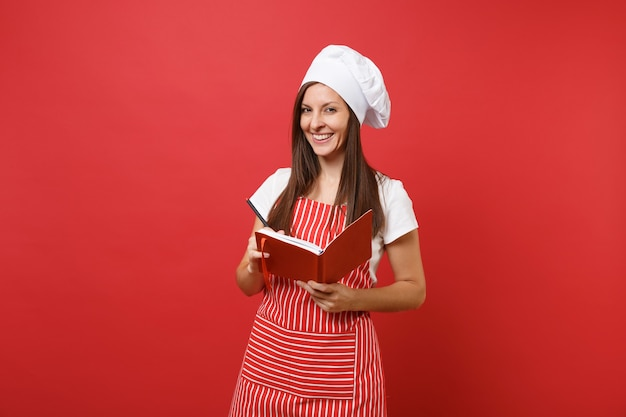 Cuoco o fornaio femminile della casalinga in cappello da cuoco unico del toque della maglietta bianca del grembiule a strisce isolato sul fondo rosso della parete. libro e penna di cucina di ricetta del blocco note della tenuta della donna sorridente. deridere il concetto dello spazio della copia.