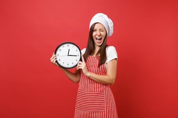 Cuoco o fornaio femminile della casalinga in grembiule a strisce, t-shirt bianca, cappello da cuoco unico del toque isolato sul fondo rosso della parete. donna sorridente che tiene in mano l'orologio rotondo sbrigati. deridere il concetto dello spazio della copia.