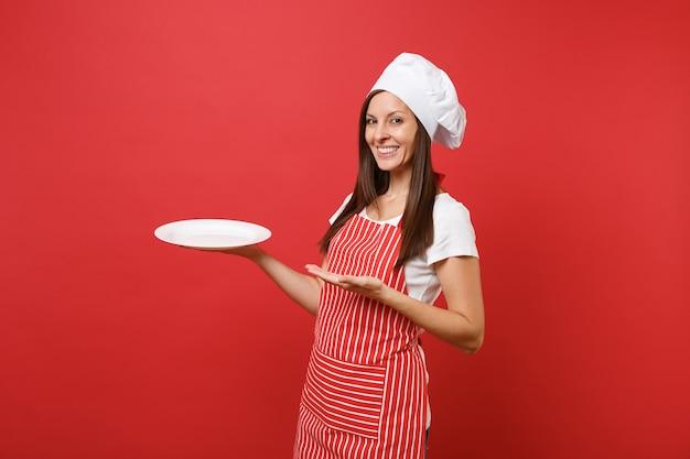 Cuoco o fornaio femminile della casalinga in grembiule a strisce, maglietta bianca, cappello del cuoco unico di toque isolato sul fondo rosso della parete. piatto rotondo in bianco vuoto della tenuta della donna con il posto per alimento. mock up copy space concept