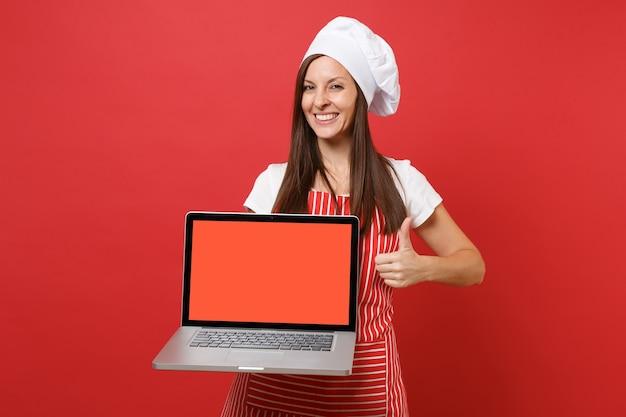 Cuoco o fornaio femminile della casalinga in cappello da cuoco unico del toque della maglietta bianca del grembiule a strisce isolato sul fondo rosso della parete. la donna tiene lo schermo vuoto del pc portatile per il contenuto promozionale mock up copy space concept