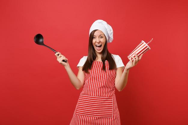 Cuoco o fornaio femminile della casalinga in grembiule a strisce, t-shirt bianca, cappello da cuoco unico del toque isolato sul fondo rosso della parete. mestolo mestolo nero della minestra della tenuta della donna, cola della tazza di plastica. deridere il concetto dello spazio della copia.