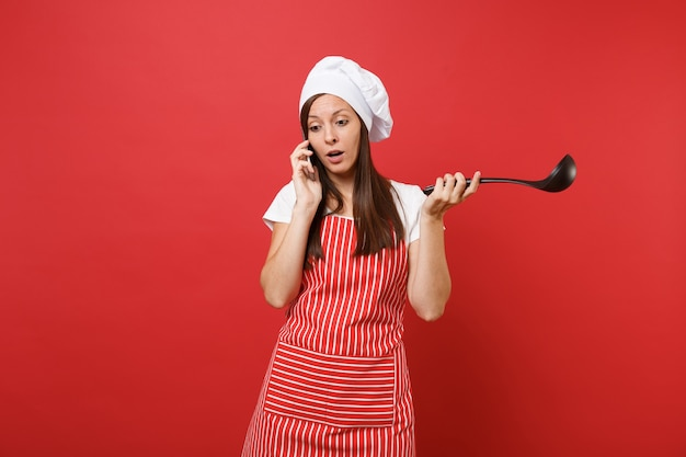 Cuoco o fornaio femminile della casalinga in cappello da cuoco unico del toque della maglietta bianca del grembiule a strisce isolato sul fondo rosso della parete. parlare del merlo acquaiolo della siviera nera della minestra della tenuta della donna sul telefono cellulare. deridere il concetto dello spazio della copia.