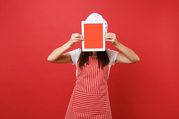 Cuoco o fornaio femminile della casalinga in cappello da cuoco unico del toque della maglietta bianca del grembiule a strisce isolato sul fondo rosso della parete. la donna tiene lo schermo vuoto del tablet pc per il contenuto promozionale mock up copy space concept