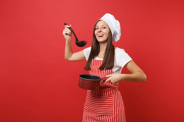 Cuoco o fornaio femminile della casalinga in cappello da cuoco unico del toque della maglietta bianca del grembiule a strisce isolato sul fondo rosso della parete. tenuta della donna che assaggia il mestolo di mestolo di minestra di casseruola vuota vuota. mock up copy space concept