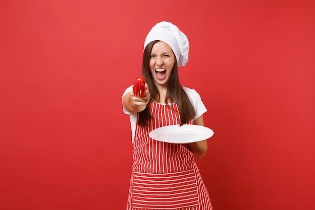 Cuoco o fornaio femminile della casalinga in grembiule a strisce, maglietta bianca, cappello del cuoco unico di toque isolato sul fondo rosso della parete. piatto bianco della tenuta della donna con la spazzola per lavare i piatti. deridere il concetto dello spazio della copia.