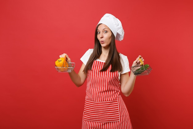 Donna casalinga chef cuoco panettiere in grembiule a righe bianco t-shirt toque cappello chef isolato su sfondo rosso parete. la donna tiene il cetriolo verde del peperone giallo nel carrello di spinta della drogheria mock up copy space concept