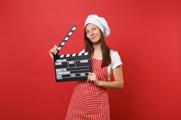 Cuoco o fornaio femminile della casalinga in grembiule a strisce, t-shirt bianca, cappello da cuoco unico del toque isolato sul fondo rosso della parete. donna che tiene il classico ciak nero per la produzione di film. deridere il concetto dello spazio della copia.