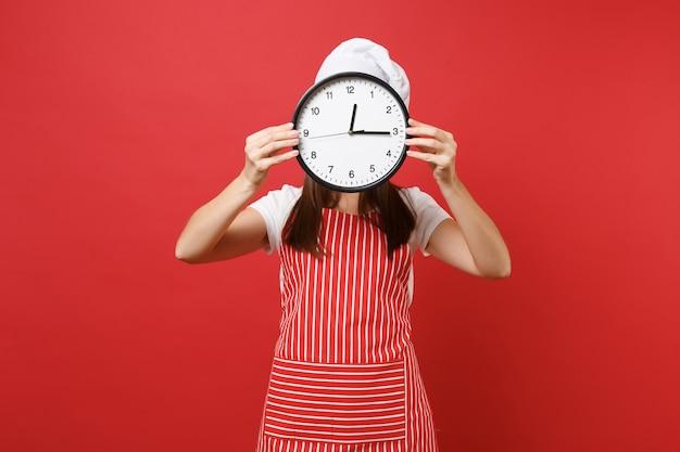 Cuoco o fornaio femminile della casalinga in cappello da cuoco unico del toque della maglietta bianca del grembiule a strisce isolato sul fondo rosso della parete. donna che tiene in mano davanti all'orologio rotondo faccia in fretta. mock up copy space concept