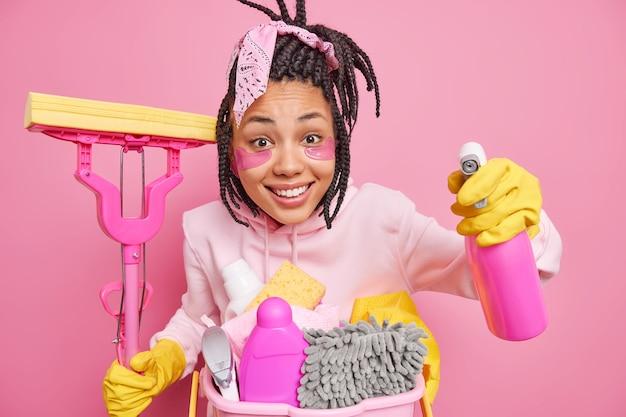 La casalinga ha un'espressione allegra tiene il detersivo per la pulizia e il mop riordina la stanza essendo di buon umore vestita casualmente isolata sul rosa