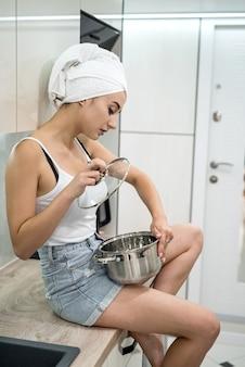 La casalinga che tiene la padella in cucina prepara la colazione dopo la doccia