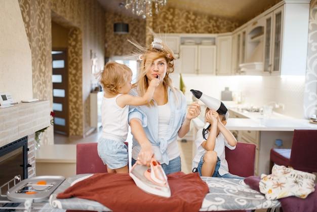 Casalinga e bambini che giocano con l'asciugacapelli sull'asse da stiro. donna con bambini che fanno i lavori domestici a casa insieme. persona di sesso femminile con figlia e figlio che si divertono nella loro casa