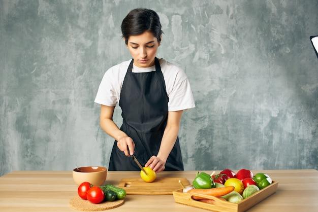 La casalinga sulla cucina che taglia le verdure ha isolato il fondo