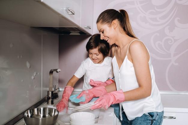 Mamma casalinga in guanti rosa lava i piatti con suo figlio a mano nel lavandino con detersivo. una ragazza vestita di bianco e un bambino ingessato pulisce la casa e lava i piatti con guanti rosa fatti in casa.