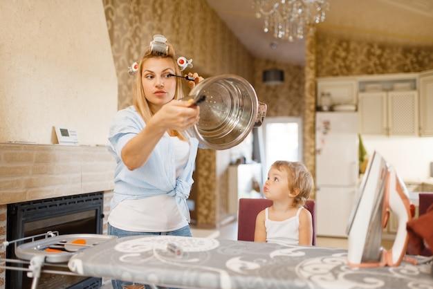 La casalinga dipinge le ciglia sull'asse da stiro, il ragazzino la guarda. donna con bambino a casa insieme