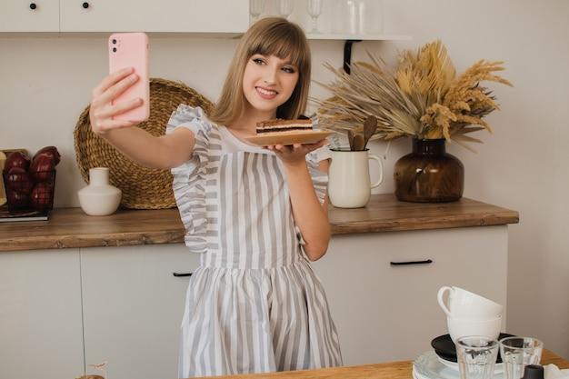 Una casalinga o un pasticcere si fa un selfie con il dessert. blog di cibo. corsi di cucina. ragazza blogger