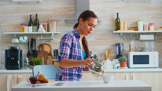 Casalinga che versa tè verde caldo in tazza al mattino seduto in cucina. donna che si gode una sana tisana a colazione usando una tazza da tè e una teiera seduta vicino al tavolo con in mano il bollitore.