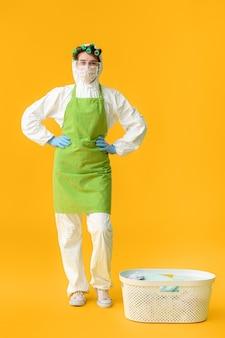 Casalinga in costume protettivo e con bucato sul colore