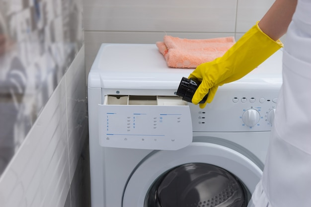 Casalinga che mette ammorbidente o detersivo in una lavatrice con una mano guantata, vista ravvicinata