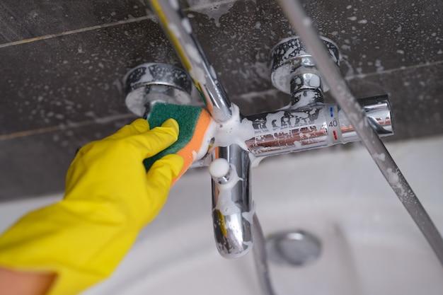 Casalinga nel rubinetto di lavaggio del guanto di gomma in bagno con il primo piano della spugna