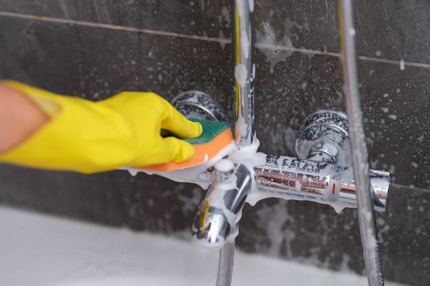 Casalinga in guanti di gomma che lava il rubinetto in bagno con detersivo facendo uso del primo piano della spugna