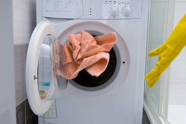 Casalinga che lancia un asciugamano nella porta aperta di una lavatrice elettrica mentre finisce le pulizie e fa il bucato