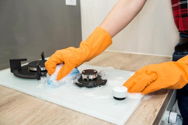 Casalinga che lava la stufa a gas con detersivo in cucina. pulizie di casa.