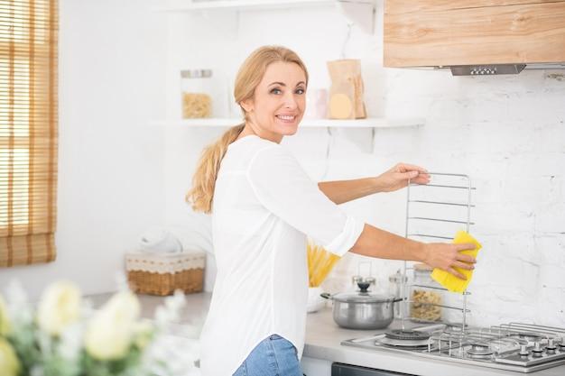 Casalinga in una camicia bianca che pulisce una stufa a gas