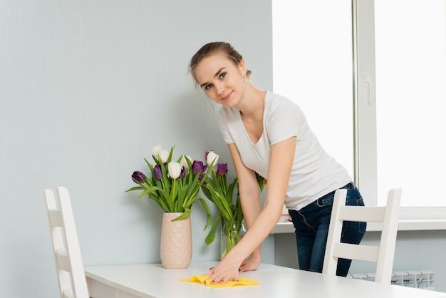 Casalinga che pulisce la polvere dal tavolo. donna fa le faccende domestiche quotidiane rispolverare usando un panno
