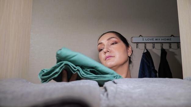 La casalinga con la crocchia per capelli mette i vestiti puliti piegati sullo scaffale