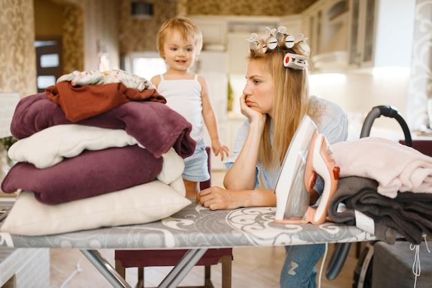 Casalinga con bambino all'asse da stiro. donna con bambino che fa i lavori domestici a casa insieme. persona di sesso femminile con figlia in casa sua